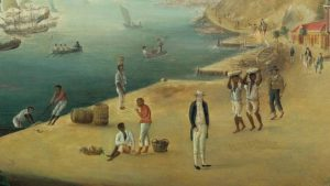 Image of the harbor of Gustavia, the capital of St Barth with Black men carrying commodities or working while one man stands idly