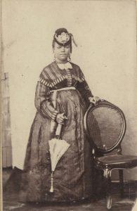 Photographie d'une femme bien habillée en Haïti debout près d'une chaise, tenant une ombrelle