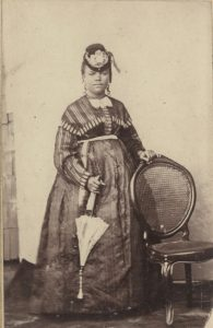 Photograph of a nicely dressed woman in Haiti standing near a chair, holding an umbrella.