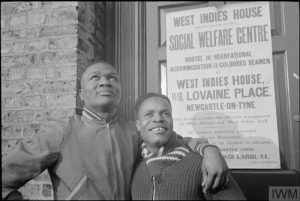 Dos hombres jóvenes vestidos con ropa de abrigo de pie delante de la Casa de las Indias Occidentales, Lovaine Place, Newcastle